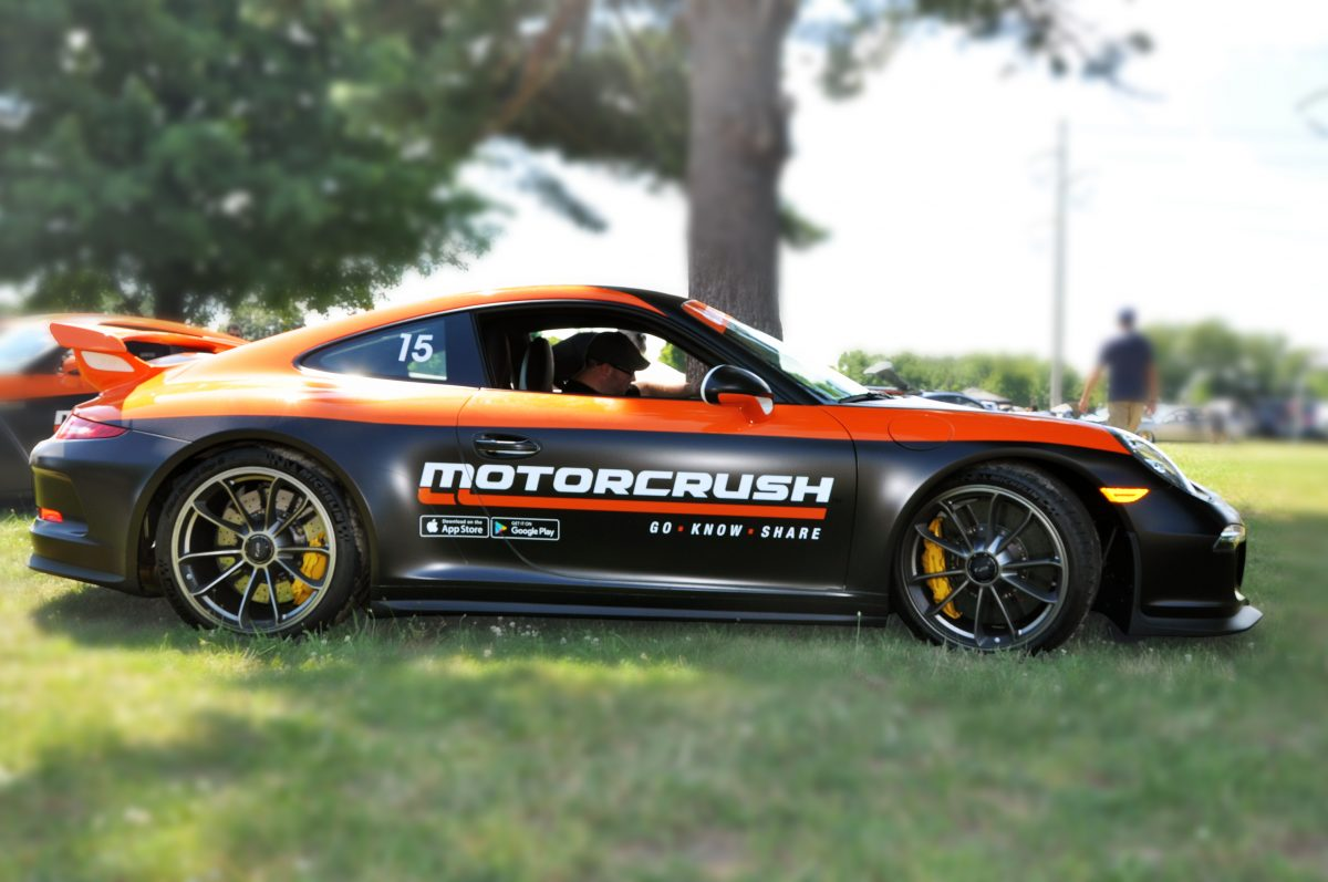 """This is a side photo of the second """"MotorCrush Car"""" – a Porsche GT with a MotorCrush branded wrap – at a local car meet. Photo is retouched for emphasis."""