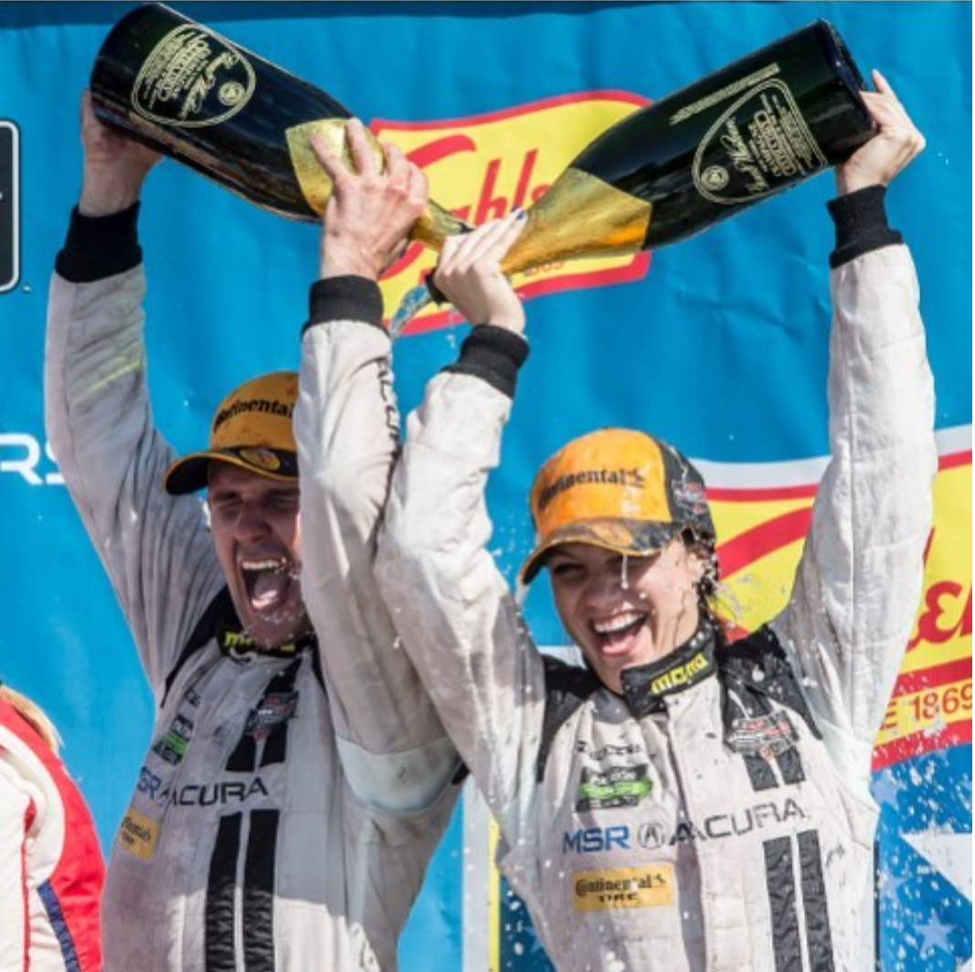This is a photo of driver Andy Lally and teammate Katherine Legge pouring champagne over one another after winning their second win in the new 2017 Acura NSX.