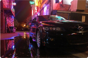 This is a night shot of a 2007 Mazda Speed 6 owned by Jared Collins under neon street lights.