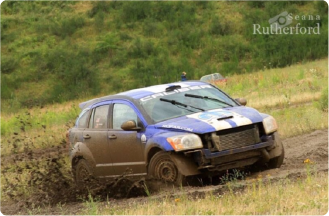 This is a picture of a blue and white striped 2006 Dodge Caliber SRT4 mudding.