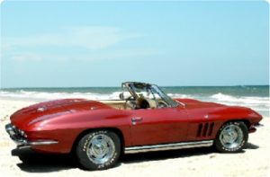 THis is a photo of a red 1965 Chevrolet Convertible Corvette on the beach.