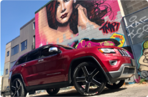 This is a shot of a 2014 Jeep Grand Cherokee owned by Benji Lovat highlighting the wheels with a stunning mural in the background.
